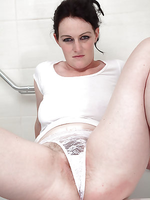 Aged solo model Andrea Foster removing wet panties from hairy muff in bathtub