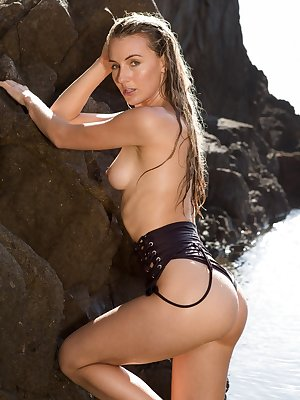 Solo model Jennifer Love slides off her swimsuit to pose nude on the rocks
