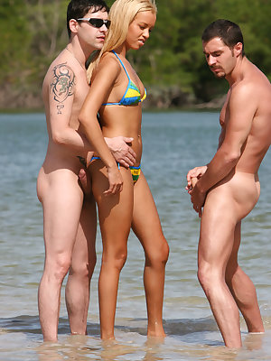 Horny blonde chick Barbie Banks bangs two guys in the shallow water at beach