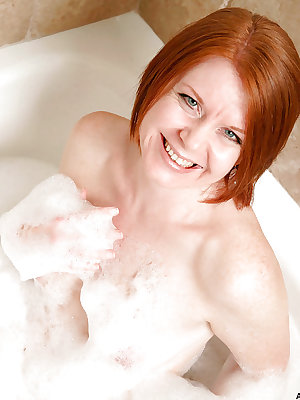 Older lady with red hair Ariana displaying pink cunt lips in bathtub
