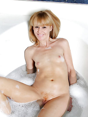 Mature lady with tiny tits masturbating wet pussy in bathtub